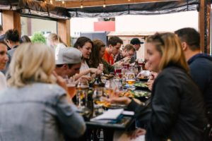 A large group of people eating and drinking in an outdoor restaurant.